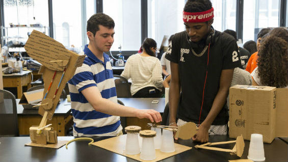 Students in the Rube Goldberg class prototype  components with cardboard and cups before 3D printing final parts.