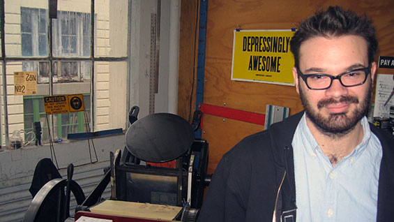 Rich Watts in front of the antique printing press used for ICD labels