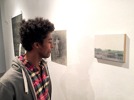 A visitor to The Cooper Union Staff Show admires a painting by Anna Hostvedt