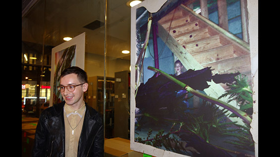 "Jackson Stack stands beside one of his photographs at his senior exhibition, ""Rooms"""