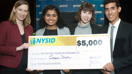 Professor Melody Baglione and seniors Kavya Udupa, Morgan Wolfe, and Billy Dayan at the CREATE Symposium after winning third place in a competition to create technology for workers with disabilities.  Isabella Pestovski (not pictured) was also a member of the Cooper team.