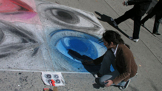 A Saturday Program student works in chalk outside the Foundation Building