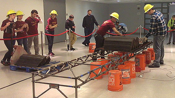 The Cooper Union team watches their work at the National Student Steel Bridge Competition