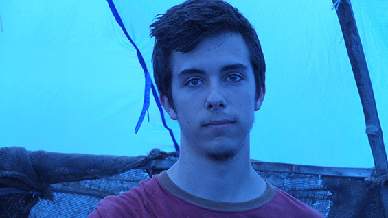 Harrison Cullen inside a shelter he helped build in Ghana covered in blue plastic. Photo by Peter North A'15