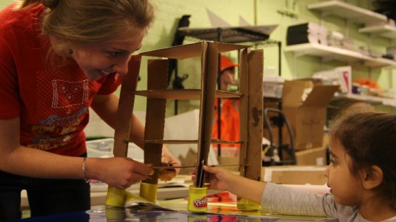 Madeline Foster's helping a young child build a structure out of cardboard