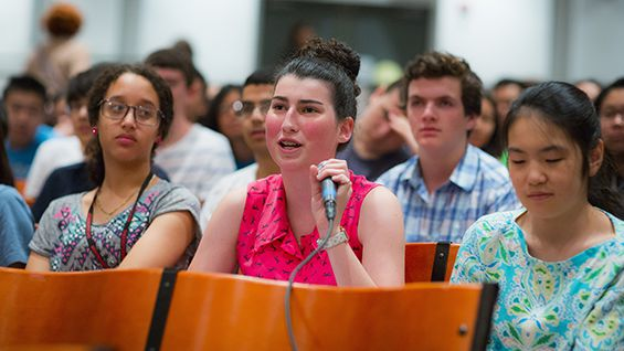 A young audience member asks a question of the panel